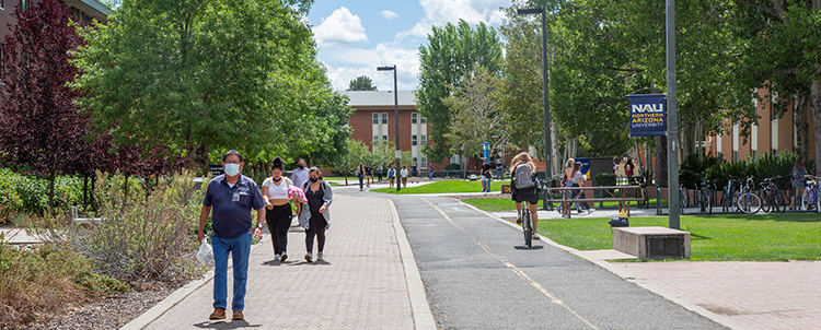 Photo of students walking on campus down a long sidewalk with trees in the distance