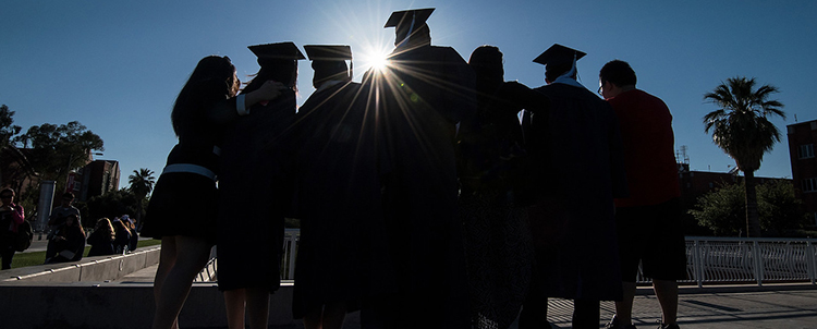 photo of college graduates in caps and gowns in silhouette