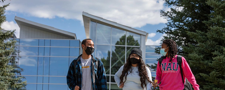Photo of three NAU students outside of a building. All of the students have on facemasks.