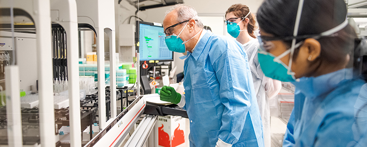 Photo three researchers in masks, safety glasses and gowns in a lab